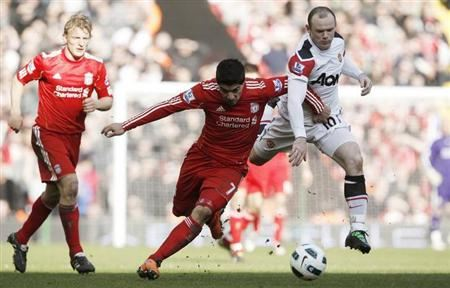 Manchester United's Wayne Rooney (R) challenges Liverpool's Luis Suarez during their English Premier League soccer match at Anfield in Liverpool, northern England, March 6, 2011. REUTERS/Phil Noble/Files